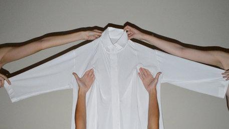 Vier Hände halten ein Hemd hoch