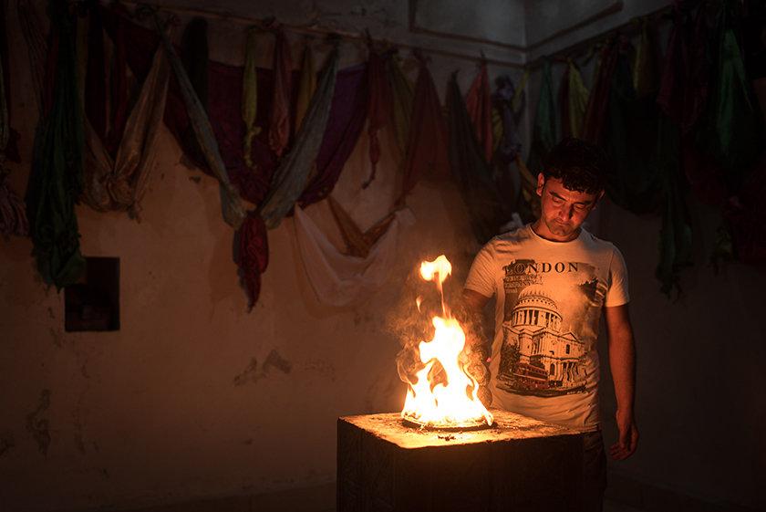 Ein junger jesidischer Mann vor einem Feuerschrein (Foto: Chris Grodotzki)