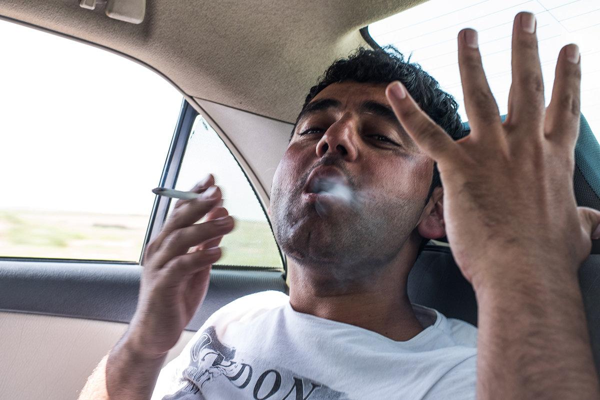 Ein rauchender Mann auf dem Rücksitz eines Autos (Foto: Chris Grodotzki)